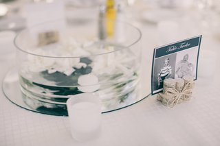 wedding-reception-table-with-white-gardenias-and-candles-floating-in-round-vase-on-top-of-a-mirror