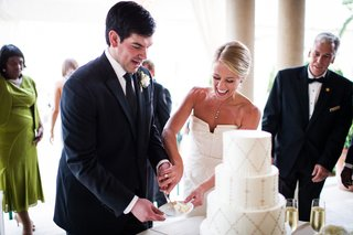 bride-and-groom-cut-cake-together-at-reception