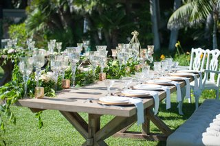garden-wedding-reception-with-rustic-wood-table-with-greenery-white-flowers-glass-candleholders