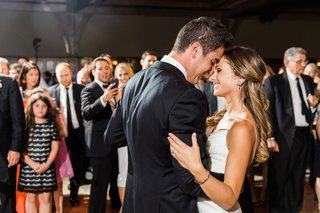 guests-watching-as-bride-and-groom-touch-foreheads-smile-during-first-dance-wedding-reception