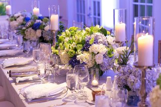 long-wedding-reception-table-with-white-and-blue-rose-hydrangea-centerpieces-greenery-candles-purple