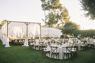 outdoor-reception-with-bistro-lights-canopy-over-head-tables-vineyard-chairs