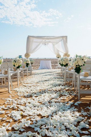 beachside-wedding-ceremony-with-white-petals-on-aisle-bundles-of-white-hydrangeas-roses-on-chairs