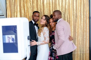 bride-and-groom-taking-pictures-in-front-of-a-shimmering-gold-curtain-photo-booth