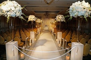 wedding-ceremony-with-tall-arrangements-of-white-hydrangeas-roses-orchids-candles-gold-chairs