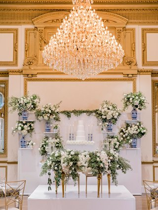 ballroom-wedding-reception-sweetheart-table-greenery-cake-wall-blue-white-vase-and-candlesticks