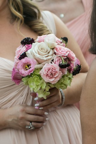 bridesmaid-holding-pink-green-and-white-flowers