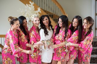 bride-in-white-robe-bridesmaids-in-pink-floral-robes-bridal-party-champagne-before-wedding