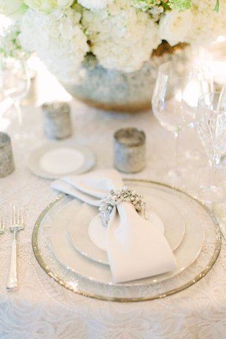 clear-charger-plate-with-white-napkin-and-white-and-silver-napkin-ring-at-wedding-reception