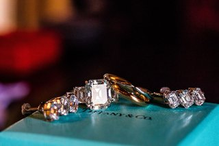 wedding-jewelry-on-top-of-tiffany-and-co-box-emerald-cut-diamond-ring-with-side-stones