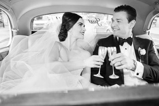 black-and-white-photo-of-bride-and-groom-in-back-of-classic-car-with-champagne-flutes