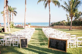 a-ceremony-space-on-lawn-in-front-of-pacific-ocean-with-chalkboard-programs