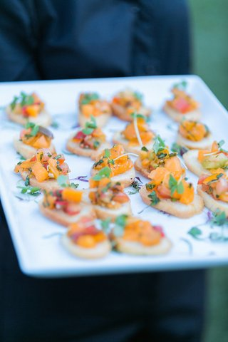 cocktail-hour-appetizers-of-crostini-with-heirloom-tomatoes-pased-by-server-on-white-tray