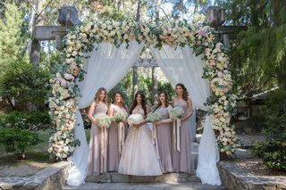 bridesmaids-in-halter-bridesmaid-dresses-champagne-taupe-gowns-ceremony-flower-arch-bouquets-ribbons