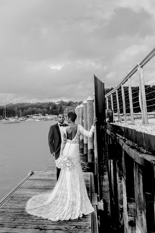 black-and-white-photo-of-bride-in-berta-wedding-dress-and-groom-in-tuxedo-on-dock