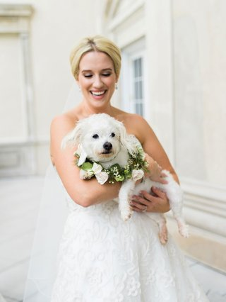 bride-in-strapless-wedding-dress-holding-white-dog-with-greenery-collar-flowers