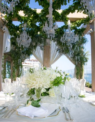 gold-rim-charger-plate-white-flowers-with-greenery-on-table-crystal-glassware-ivory-drapery-greenery