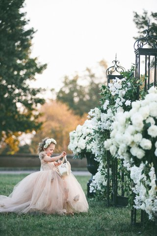 flower-girl-in-champagne-tulle-ball-gown-with-basket-and-flower-crown-gates-with-white-flowers