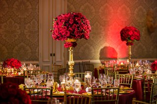 tall-centerpiece-of-red-roses-held-up-by-gold-stand