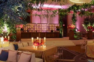 wedding-weekend-welcome-dinner-decorated-with-greenery-candles-and-orange-and-pink-flowers