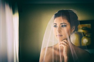 a-bride-looks-out-the-window-with-her-sheer-white-veil-drawn-over-her-face