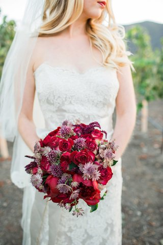red-purple-pink-bouquet-flowers-bride-in-jim-hjelm-dress-red-lips-outside-at-vineyard