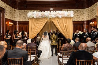 indoor-ceremony-with-dark-wood-wainscoting-ceremony-altar-with-white-and-blush-flowers-gold-drape