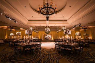 indian-wedding-reception-ballroom-chandelier-dance-floor-square-tables-high-low-centerpieces-pink