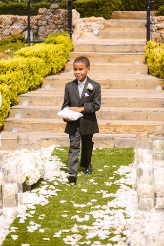 ring-bearer-in-dark-grey-suit-smiles-while-walking-down-aisle-with-ring-pillow