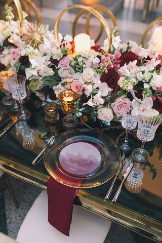 clear-charger-plate-on-mirrored-table-paired-with-burgundy-napkin