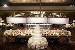 five-layer-white-wedding-cake-with-frosting-in-front-of-head-table-with-white-cream-flowers