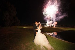 bride-in-monique-lhuillier-wedding-dress-and-groom-in-front-of-helicopter-and-fireworks-display