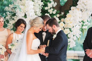 wedding ceremony garden officiant bridesmaids in front of tree decorated with white rose flowers