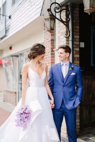 bride-in-hayley-paige-wedding-dress-layered-skirt-bouquet-of-lavender-stock-groom-in-blue-suit