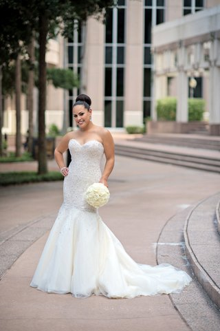bride-holding-bouquet-wearing-strapless-bridal-gown