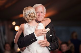 a-blushing-bride-hugs-her-father-after-their-father-daughter-dance-at-her-wedding-reception