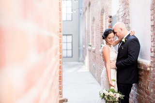 wedding-portrait-bride-in-claire-pettibone-wedding-dress-holding-bouquet-with-groom-embracing