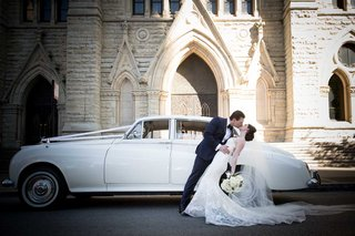 bride-and-groom-kiss-dip-in-front-of-white-classic-wedding-car-in-front-of-chicago-church