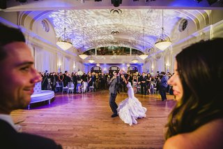 bride-and-groom-dancing-in-background-of-photo
