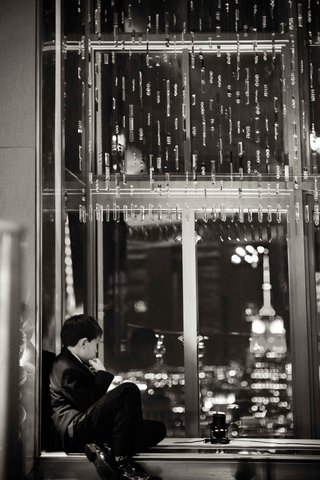 black-and-white-photo-of-young-boy-looking-out-window-to-views-of-new-york-city-wedding-reception