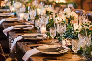 long-wood-table-with-greenery-runner-cut-vintage-glassware-napkin-greens-vines-reception-table
