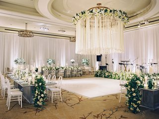 wedding-reception-white-dance-floor-chandelier-crystal-and-satin-ribbon-white-flowers-greenery