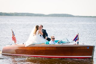 bride-and-groom-kiss-on-small-motor-boat-on-the-water