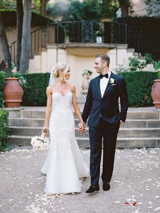 a-bride-in-a-soft-trumpet-wedding-gown-holding-hands-with-her-groom-in-classic-black-tuxedo-outside