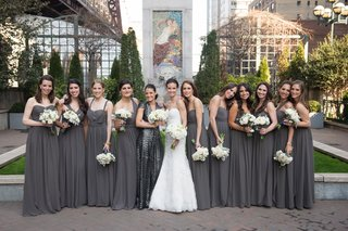 a-bride-in-a-white-lace-wedding-gown-stands-with-her-bridesmaids-clad-in-gray-gowns-white-bouquets