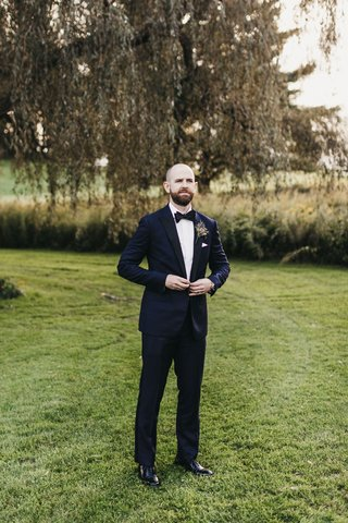 groom-buttoning-midnight-blue-tuxedo-from-bonobos-while-standing-in-a-field