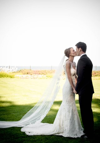 bride-kissing-groom-in-pony-tail-with-lace-trim-veil