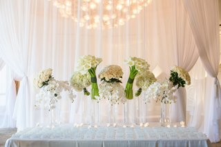 wedding-reception-escort-card-table-seating-assignments-white-drapery-collections-of-white-flowers