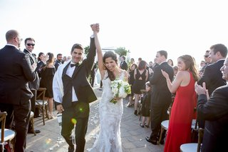bride-in-monique-lhuillier-wedding-dress-and-groom-hold-hands-celebrate-after-getting-married-aisle
