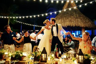 bride-and-groom-kiss-while-doing-circle-dance-at-reception